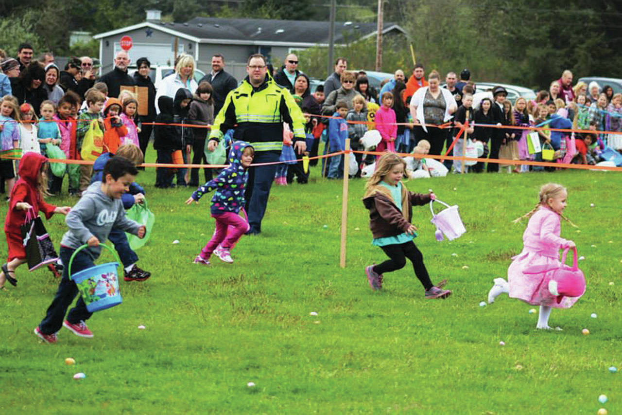 Angelo Bruscas/North Coast News: Brian Ritter supervises as the wave of younger kids head out through the field laden with Easter Eggs at the Ocean Shores Elementary School.