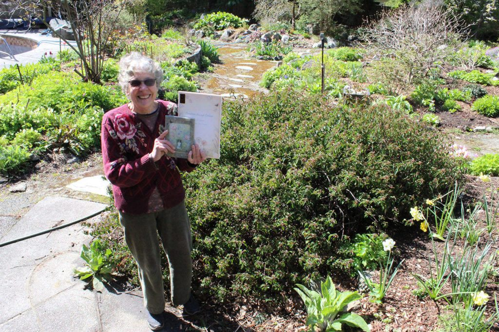 Helen Stewart holds up a pair of her books – A Garden's Echo and Creation Through Colour – in her Tudor Avenue garden. Stewart's home at 2875 Tudor Ave. will be one of the stops on the Hills to Shore Artists Tour May 12 and 13. (Dan Ebenal/News Staff)