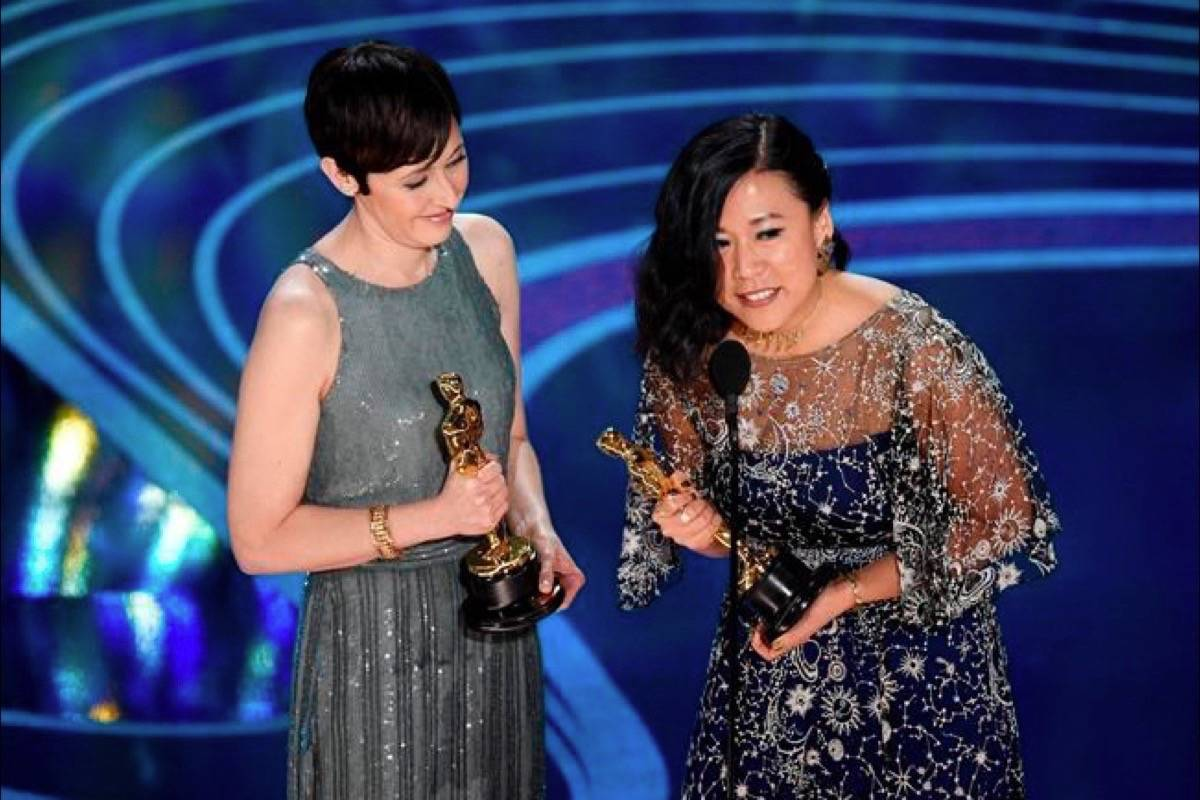"""Becky Neiman-Cobb, left, and Domee Shi accept the award for best animated short for """"Bao"""" at the Oscars on Sunday, Feb. 24, 2019, at the Dolby Theatre in Los Angeles. (Photo by Chris Pizzello/Invision/AP)"""