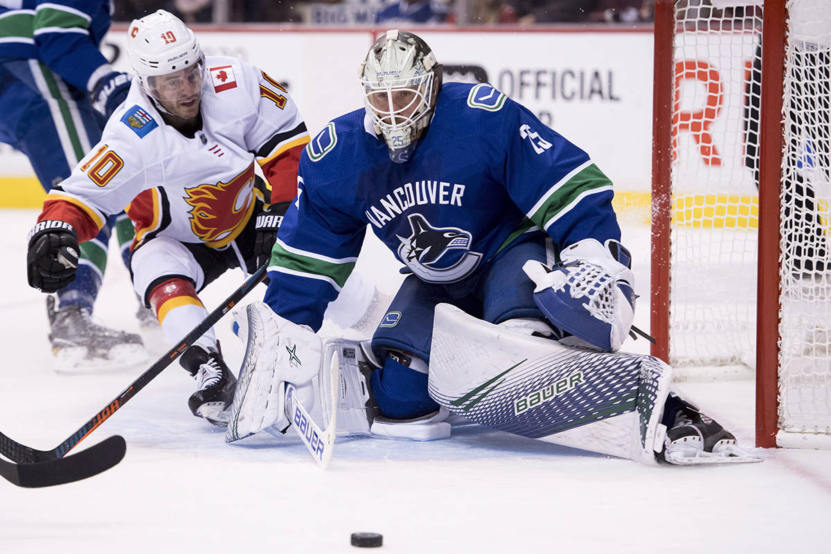 Calgary Flames center Derek Ryan (10) tries to get a shot past Vancouver Canucks goaltender Jacob Markstrom (25) during first period NHL action at Rogers Arena in Vancouver, Wednesday, Oct, 3, 2018. THE CANADIAN PRESS/Jonathan Hayward