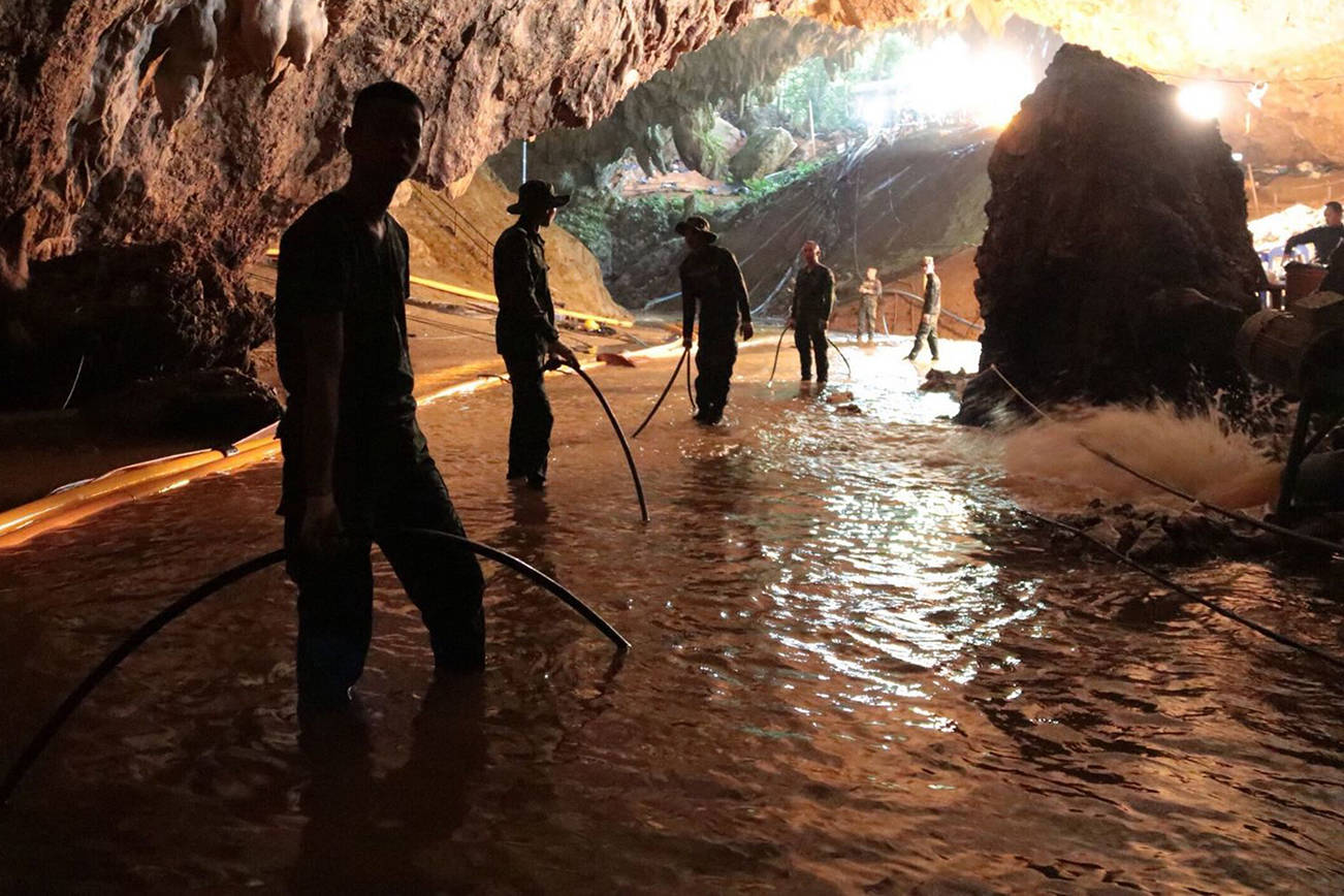 In this undated photo released by Royal Thai Navy on Saturday, July 7, 2018, Thai rescue teams arrange water pumping system at the entrance to a flooded cave complex where 12 boys and their soccer coach have been trapped since June 23, in Mae Sai, Chiang Rai province, northern Thailand. (Royal Thai Navy via AP)
