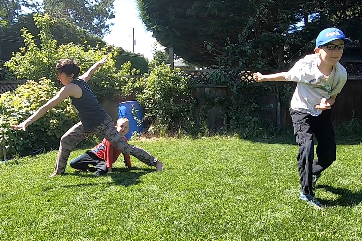 Shannon Moreno and her sons Mattias and Edward Johansson (from left) dance in their backyard. Crimson Coast Dance Society is asking families to send in videos of themselves dancing to be compiled and shown at this year's Infringing Dance Festival. (Photo supplied)